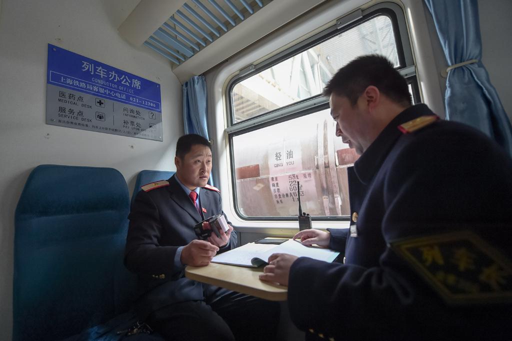 ,邵强(左)在阜阳至北京的K4132次列车上与列车长进行发车前的高清图片