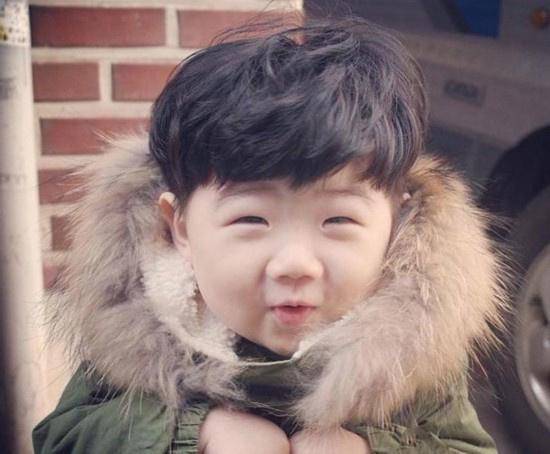 """肉嘟嘟的小脸蛋上挂着韩国男生标志性的""""单眼皮小眼"""",笑起来咪成一条"""