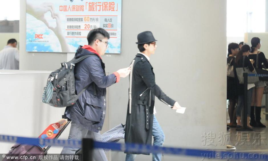 何炅戴黑超穿长外套现身机场 大步流星赶飞机