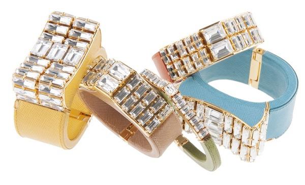 设计灵感来源于上世纪四十年代高级珠宝的创意和诱人魅力,Prada 推出了一系列颇具现代感的珠宝,包括手环、手镯、手链和耳饰。 每一件都采用手工工艺精心打造而成的高级珠宝,细节精美;拥有大胆的色彩和外形,并选用出人意料的材质制作。 该系列融入了Prada 标志性的Saffiano 纹理皮革,颜色丰富多彩,包括橙色、翠绿色和宝石绿色,运用几何状水晶展现其大胆外形,这样的设计灵感来源于装饰派艺术时代和自然界。 取自2014年春季男女服饰系列的木槿花图案出现在了Saffiano 皮革手链和水晶耳坠之上。颇具异国情