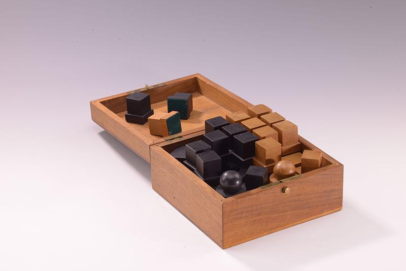 作品描述:这套象棋是魏玛包豪斯先后生产的三套象棋中的最早版本。后来经过微小的改动,这套象棋在德绍包豪斯投入小型批量生产。柏林包豪斯档案馆收藏有包豪斯院长沃尔特•格罗皮乌斯遗留下来的,在德绍包豪斯生产的最终版本的样本。关于这套象棋的设计方案,哈特维希自己如此解释:新的棋子是由三个基本的几何形体组成,即立方体、圆柱体和球体。它们单一出现,或者组合在一起,通过棋子的造型表现其走法,通过体积体现其身份。棋子的身份是通过高度和体积区分的:国王和王后最大,兵是最小的。马和象大小相同,它们的体积是车的一半。