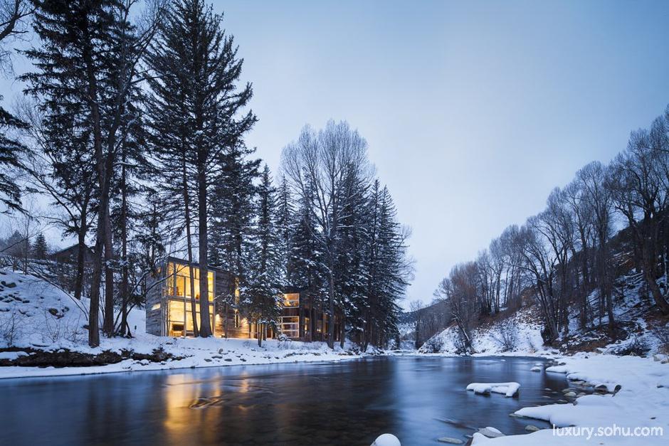 春天有清澈的流水潺潺而过,冬天则有浮着冰块的雪水缓缓流动,在这个狭窄的河岸,Piampiano别墅创造出一个如仙境般的居住体验,被模糊的内外边界,形成了与环境互动的别墅。   高大的针叶树是Piampiano别墅的一部分,别墅外层覆盖的木板也正好反映了树木的纹理和颜色。内饰采用了简单的白色涂料和枫木,自然的光影在室内投射得异常好看,同时浅色的内饰跟纹理较深的外墙形成了对比。