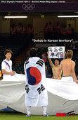北京时间8月11日,韩国男足2-0击败日本队取得男足铜牌之后,一位韩国队队员举着一面韩国国旗,国旗上...
