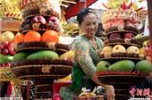 当地时间2013年10月23日,印尼巴厘岛民众手捧鲜花水果祈祷,庆祝加隆安节。加隆安节又称地球节,是...