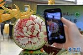"""5月25日,在第27届北京大兴西瓜节的""""西瓜创意美食大赛""""上,一名参观者用手机拍摄西瓜雕刻作品。当日..."""