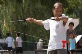 """陶然亭公园内不同方式健身的市民,公园内的民间合唱团印制了""""北京欢迎你"""